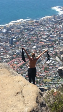 Naked girl poses topless towards the city of Cape Town