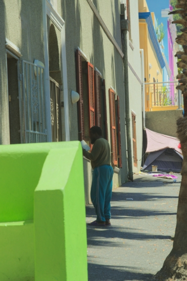 A man praying in front of a mosque in bo-kaap, Cape Town, South Africa, with a tent, homeless person, colorful houses,