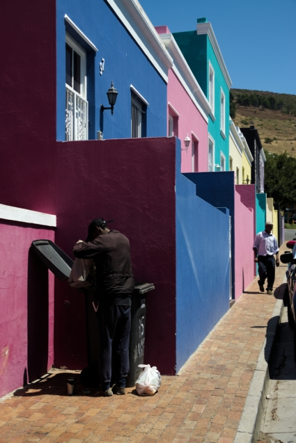 Homeless person going through rubbish looking for food in bo-kaap in Cape Town, South Africa