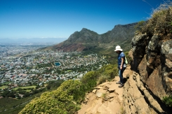 a person staring down on the edge of the trail to lions head, cape town, south africa, a view on the city and table mountain