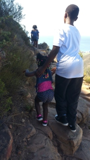 A young black kid is leading his sister on the trail down from Lions head, dangerous, reckless