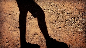 A shadow of legs on the ground, soil, tramping man logo